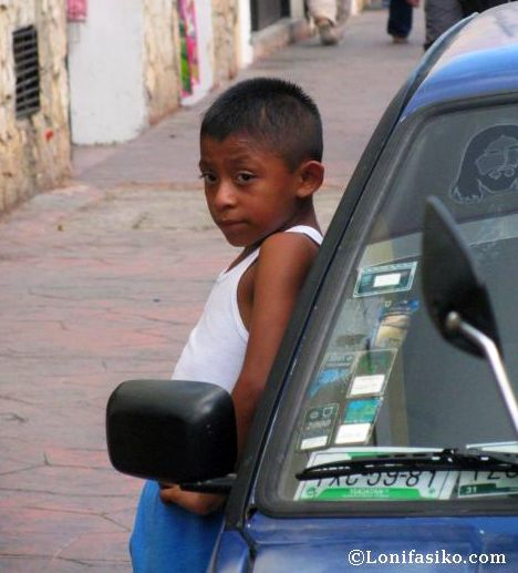 Niño vallisoletano esperando apoyado en coche