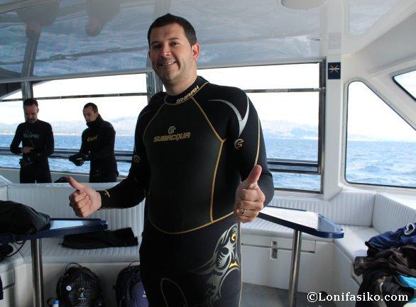 Lonifasiko embutido en un neopreno dispuesto a nadar entre atunes
