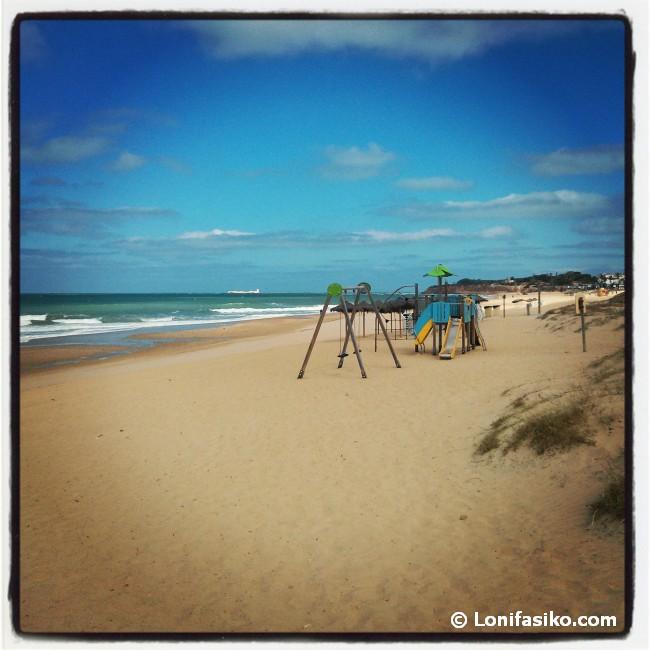 Zona de columpios en la Playa de La Barrosa. Al fondo, el Castillo de Sancti Petri