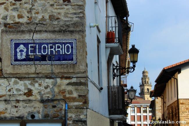 Viejo cartel de la villa de Elorrio, con la iglesia al fondo