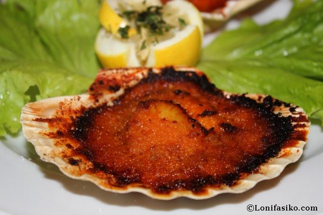 Vieira gratinada al horno, con un relleno y salsa de la casa