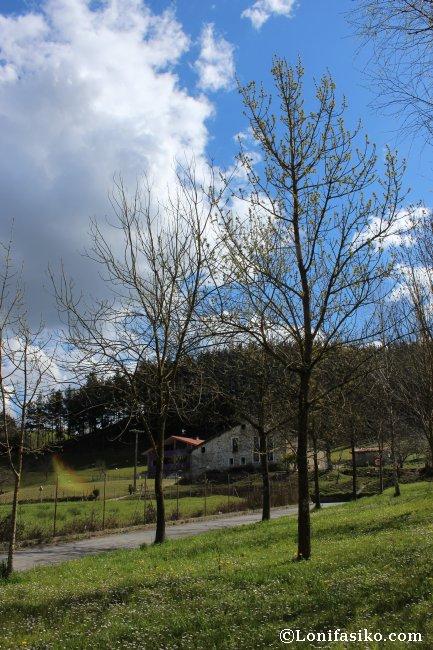 Vista hacia la vía verde del Urola y un antiguo caserío desde el merendero